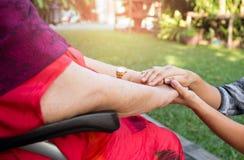 Caretaker pushing senior woman in wheel chair Stock Photography