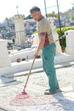 Caretaker raking in cemetary. Caretaker raking in the cemetary Stock Images