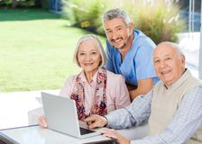 Caretaker And Senior Couple With Laptop At Nursing. Portrait of smiling male caretaker and senior couple with laptop at nursing home porch royalty free stock photos