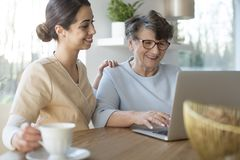 Caretaker and senior with laptop. Tender caretaker closing the generation gap and teaching a smiling senior women the use of Internet on a laptop while sitting royalty free stock photo