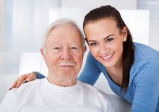 Caretaker with senior man at nursing home. Portrait of young female caretaker with senior men at nursing home Royalty Free Stock Image