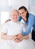 Caretaker with senior man at nursing home. Portrait of young female caretaker with senior men at nursing home stock photo