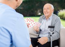 Caretaker And Senior Man Playing Cards At Nursing. Male caretaker and senior men playing cards while sitting on couch at nursing home porch royalty free stock photos