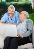 Caretaker With Senior Man Using Laptop On Couch Stock Image