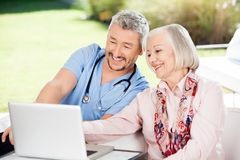 Caretaker And Senior Woman Using Laptop Stock Image