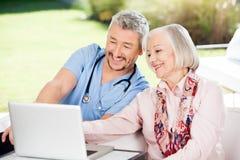 Caretaker And Senior Woman Using Laptop. Happy caretaker and senior women using laptop at nursing home porch stock image