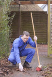Caretaker service. Man at work. groundskeeper (caretaker service) cleaning a garden path royalty free stock photography