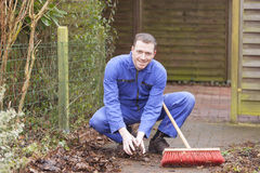 Caretaker service. Man at work. groundskeeper (caretaker service) cleaning a garden path royalty free stock photos