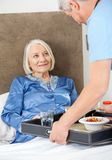 Caretaker Serving Breakfast To Happy Senior Woman. Male caretaker serving breakfast to happy senior women on bed in nursing home Royalty Free Stock Photo