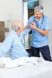 Caretaker Supporting Senior Man To Get Up From Bed. Male caretaker supporting senior men to get up from bed at nursing home stock images