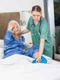 Caretaker Using Hot Water Bottle On Senior Woman. Female caretaker using hot water bottle on senior woman's leg at nursing home royalty free stock image