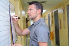 Caretaker writing on whiteboard. Caretaker writing on a whiteboard stock images