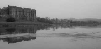 Carew Castle & Mill on a Misty Morning. Carew Castle & Mill Reflecting in the water on a misty morning, Pembrokeshire royalty free stock images