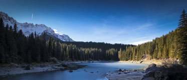 Carezza lake in winter with frosty surface. In the background there are a pinewood and some snowy mountains stock images