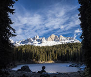 Carezza lake in winter with frosty surface. In the background there are a pinewood and some snowy mountains. Two black trees on the left and right side Royalty Free Stock Image