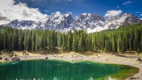 Carezzameer in het Dolomiet in de lente met groen bos en sneeuw op bergen stock videobeelden