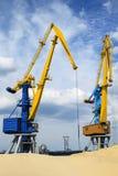 A carga cranes no porto fluvial perto do monte da areia Fotografia de Stock