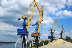 A carga cranes no porto fluvial perto do monte da areia Imagens de Stock Royalty Free