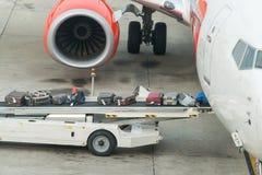 Carga da bagagem em um plano em um aeroporto imagem de stock