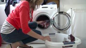 A carga da mulher veste-se na máquina de lavar vídeos de arquivo