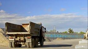 Carga de espera do caminhão vazio na estrada da construção filme