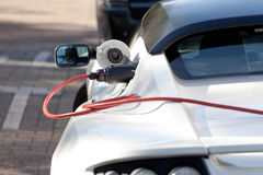 Carga de un coche de deportes eléctrico Imágenes de archivo libres de regalías