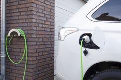 Carga de un coche eléctrico en casa Imagenes de archivo