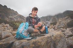 Carga de un teléfono móvil en un rastro de montaña Fotos de archivo libres de regalías