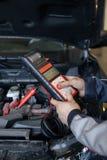 Carga del acumulador Manos y terminales Reparación del coche servicio Fotos de archivo