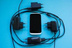Carga inalámbrica para el smartphone en un fondo azul, concepto fotos de archivo libres de regalías