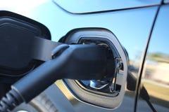 Carga negra del coche eléctrico en casa Fotos de archivo libres de regalías