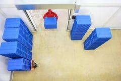 Carga - o trabalhador no azul uniforme vermelho da carga contém Fotografia de Stock