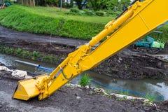 Cargador amarillo de la retroexcavadora que hace el canal para inundar la prevención foto de archivo