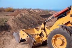 Cargador de excavador que trabaja en el área de tierra, proceso de excavación Compartimiento amarillo imagen de archivo libre de regalías