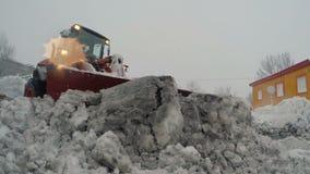 Cargador de la rueda de la parte frontal que despeja nieve y el hielo mojados del camino, mantenimiento de carreteras del inviern