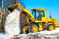 Cargador de la rueda que descarga nieve durante obras por carretera Foto de archivo libre de regalías