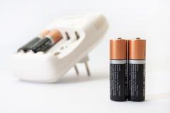 Cargador y baterías de batería en un fondo blanco Fotos de archivo
