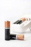 Cargador y baterías de batería en un fondo blanco Fotografía de archivo