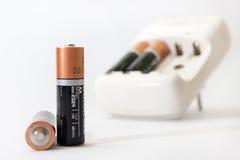 Cargador y baterías de batería en un fondo blanco Imagen de archivo
