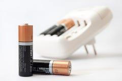 Cargador y baterías de batería en un fondo blanco Imagenes de archivo