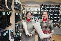 Cargadores del programa inicial que hacen compras de las mujeres en el zapato Imagenes de archivo