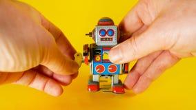 Cargas del hombre un robot del metal del vintage para hacer que él camina en el fondo amarillo, ideal de la cantidad para los tem almacen de metraje de vídeo