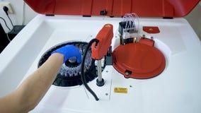 Cargas del técnico de laboratorio que analizan la máquina, poniendo una bandeja con las muestras almacen de metraje de vídeo