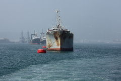 Cargo anchored in front of mist Stock Photos