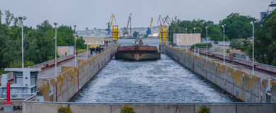 Cargo barge bulk. A cargo barge in the lock of a water dam Stock Image