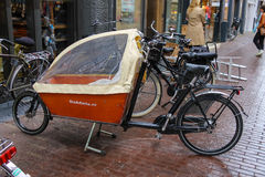 Cargo bike with protect tent parking on the street in Haarlem Royalty Free Stock Photography