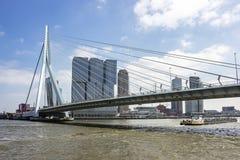 A cargo boat is just passing the erasmus bridge in Rotterdam.  stock photos