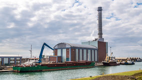 Cargo boat next to a power station Stock Photo