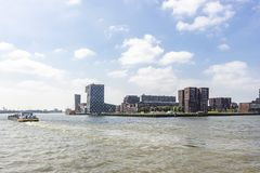 A cargo boat on the river Maas passes the building of the Netherlands Maritime University stock image