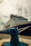 Cargo Boat`s Bow and Rope Tied to Blue Bollard Royalty Free Stock Images